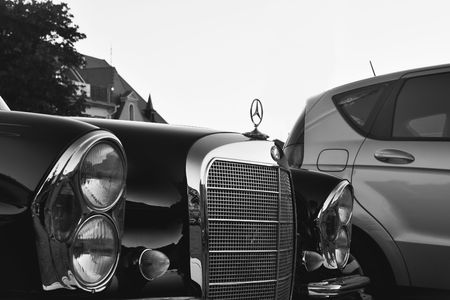 Mercedes Benz logo on a black vintage car. Mercedes-Benz is a German automobile producer. The brand is used for luxury automobiles, buses, coaches and trucks. Black white filter.