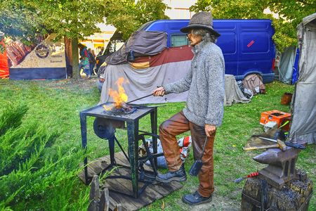 Street performer as blacksmith.  Street performers can fool passersby and entertain tourists. Editorial