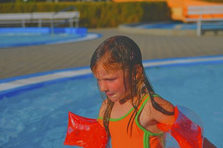 Happy little girl enjoying summer day in the swimming pool. Cute girl with inflatable armbands in small swimming pool.  Summer and happy chilhood concept. Stock Photo