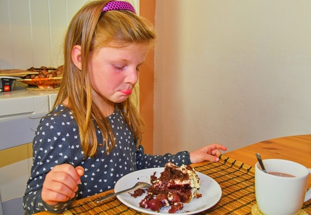 Little girl looking on her birthday cake. Small girl celebrating her six birthday. Little girl is eating cake