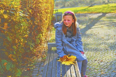 Little girl wearing retro coat and sitting on bench in park in autumn. Small girl is holding colorful autumn leaves. Autumn concept. Autumn foliage