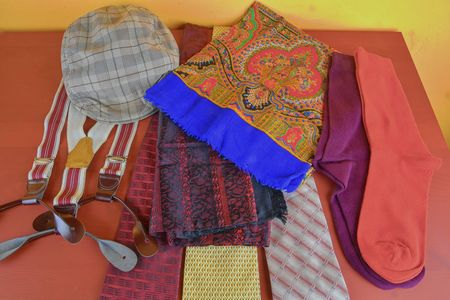 Man garments. Clothing concept for men. Colorful socks, ties, braces, scarfs and checked flat cap on claret background. Classical concept of men garments. Close-up Stock Photo