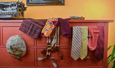Man garments. Clothing concept for men. Colorful socks, ties, braces, scarfs and checked flat cap on claret background. Classical concept of m ens  garments. Wintage typewriter and man clothing.