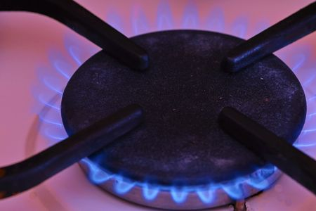 A blue flame from a gas cooktop burner. Stove turbo burner with burning flame closeup