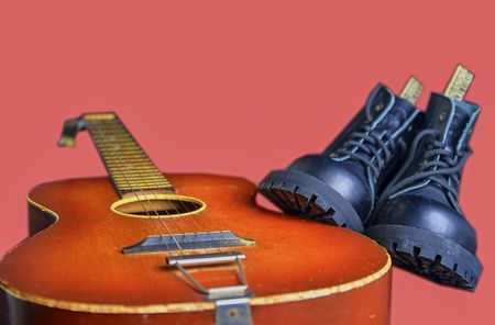 Rock and roll concept. Black boots and acoustic guitar. Rock and roll boots on pink background 免版税图像