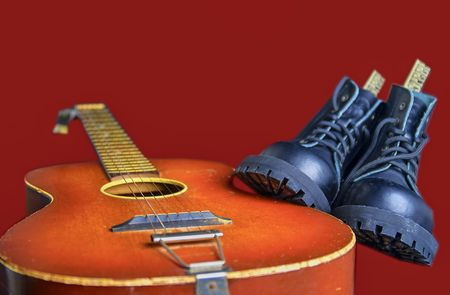 Rock and roll concept. Black boots and acoustic guitar. Rock and roll boots on claret background