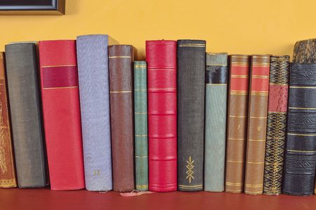 Wooden shelf with historic,decorated, vintage books. Old books on yellow and claret background