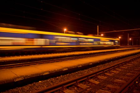 Passenger train on railroad tracks at night  Blurred motion