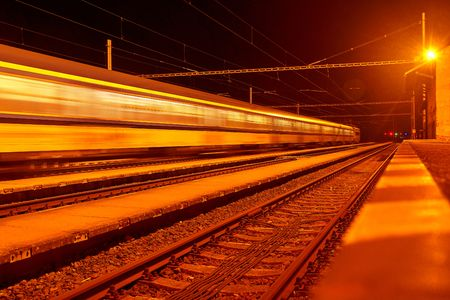 High speed passenger train on tracks with motion blur effect at night. Railway station in the Czech Republic.