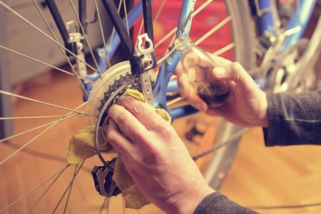 Man lubricating bicycle chain and maintaining for the new season. Oiling and repairing of bicycle drive 스톡 콘텐츠