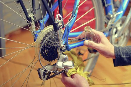 Close-up of a mans hand, lubricate the bicycle chain of a bike with a special oil in the home workshop