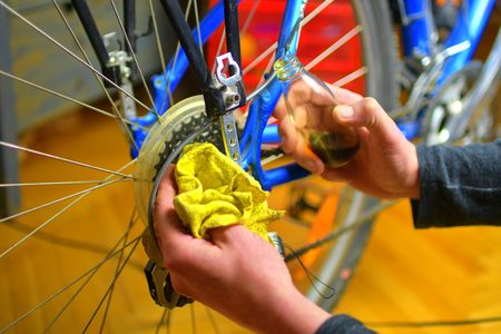Mechanic in a bicycle repair shop oiling the chain of a bike. Man maintaining his bicycle for the new driving season. Working process 스톡 콘텐츠