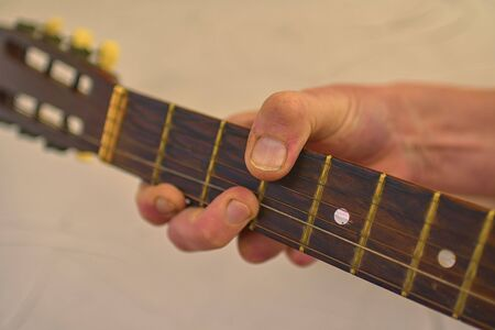 Hand of man playing the old acoustic guitar. Old guitar head with tuning pegs
