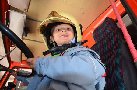 Little boy acting like a fireman. Boy sitting in a real fireman car. Happy adorable child boy with fireman hat sitting in red fire truck looking out. Dreaming of future profession. Fire safety, life protection lessons