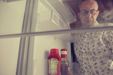 Senior man opening a refrigerator with little food. Selective focus. Hungry man looking for a late night meal in an empty fridge