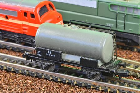 Railway tanker truck. Train hobby model on the model railway. Railroad platforms for transporting of liquid goods and products such as oil, gas, diesel. Close-up. 免版税图像