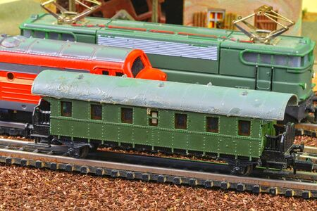 Close-up of model railway carriage on the rail tracks. Perfect model of the electric locomotive and diesel locomotive. Train hobby model on the model railway. Close-up.