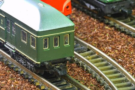 Close-up of model railway carriage on the rail tracks. Perfect model of the diesel locomotive. Train hobby model on the model railway. Close-up. Stock Photo
