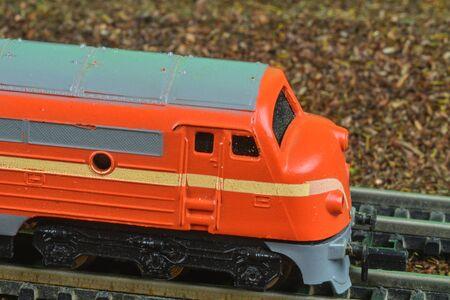 Perfect model of the orange diesel locomotive. Train hobby model on the model railway. Close-up 免版税图像