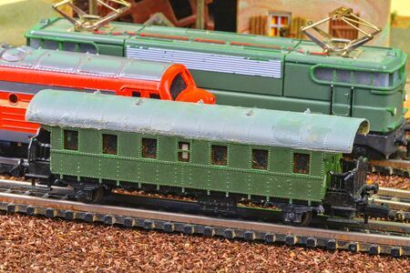 Close-up of model railway carriage on the rail tracks. Perfect model of the electric locomotive and diesel locomotive. Train hobby model on the model railway. Close-up 免版税图像