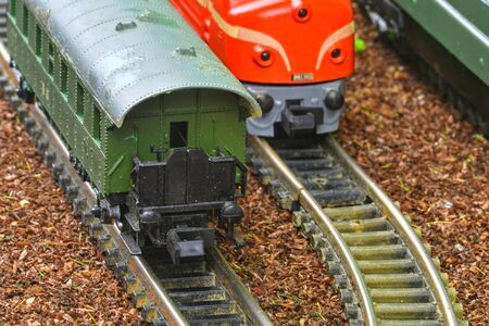 Close-up of model railway carriage on the rail tracks. Perfect model of the diesel locomotive. Train hobby model on the model railway. Close-up Stock Photo