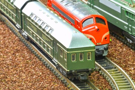 Close-up of model railway carriage on the rail tracks. Perfect model of the diesel locomotive. Train hobby model on the model railway. Close-up 免版税图像