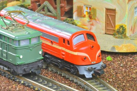 Perfect model of the electric locomotive and diesel locomotive. Train hobby model on the model railway. Close-up