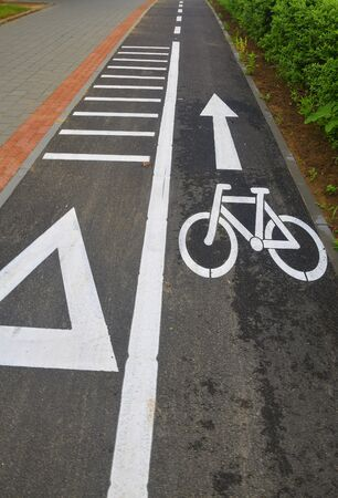 City lane for cyclists and skaters. Bicycle signs on the road. Bicycle road with arrow. Bicycle and modern ecological public movement Stock Photo