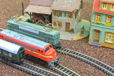 Train hobby models on the model railway. Close-up of model railway carriage on the rail tracks. Perfect model of the diesel locomotive. Train hobby model on the model railway. Close-up