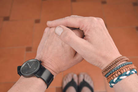 Man wearing a bracelet made of rope, wood, leather, beads and colored rope sack. Black watch on man hand. Hipster fashion on tiled flooring background.