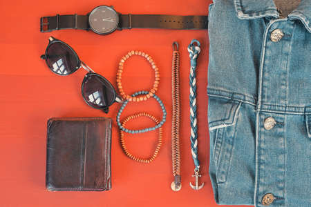 Top view of men accessories. Hipster or modern man concept. Accessories for going for a walk. Male fashion accessories, flat lay on coral pink background.