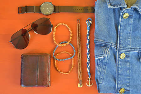 Top view of men accessories. Hipster or modern man concept. Accessories for going for a walk. Male fashion accessories, flat lay on coral pink background. Wallet, bracelets, sunglasses - shades, watch, denim jacket.  Stock Photo