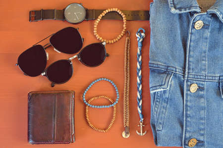 Top view of men accessories. Hipster or modern man concept. Accessories for going for a walk. Male fashion accessories, flat lay on coral pink background. Wallet, bracelets, sunglasses - shades, watch, denim jacket.