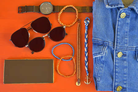 Top view of men accessories. Hipster or modern man concept. Accessories for going for a walk. Male fashion accessories, flat lay on coral pink background. Wallet, bracelets, sunglasses - shades, watch, denim jacket and mobile phone. Stock Photo
