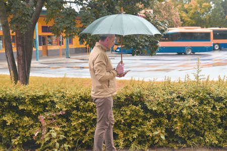 Mature caucasian man wearing a pastel jacket is using a smartphone under an umbrella. Man waiting on a bus, texting on mobile phone in a rainy day. Rainy day in a local town. Stock Photo