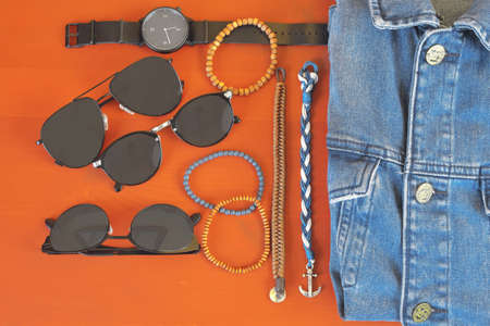 Top view of men accessories. Hipster or modern man concept. Accessories for going for a walk. Male fashion accessories, flat lay on coral pink background. Bracelets, sunglasses - shades, watch - ticker, denim jacket .