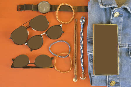 Top view of men accessories. Hipster or modern man concept. Accessories for going for a walk. Male fashion accessories, flat lay on coral pink background. Bracelets, sunglasses - shades, watch - ticker, denim jacket and mobile phone. Stock Photo