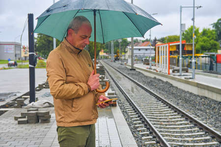 Portrait of a mature traveller texting on smartphone with an umbrella standing on the platform of a train station. Unfinished railway line. When the train arrives.. Funny concept of futile situation