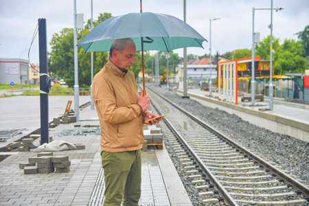 Portrait of a mature man with an umbrella standing on the platform of a train station. Unfinished railway line. When the train arrives.. Funny concept of hopeless situation