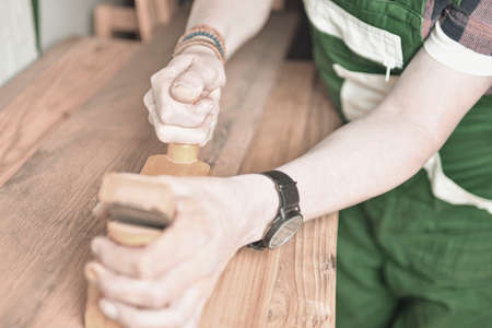 Close up of a carpenter planing a plank of wood with a hand plane. Carpenter working with plane on wooden background. Young carpenter wearing bracelets