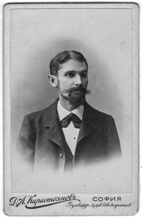 SOFIA, BULGARIA - CIRCA 1910: Vintage cabinet card shows portrait of the midle-aged man with mustache, full beard. Photo was taken in a photo studio. Edwardian era.