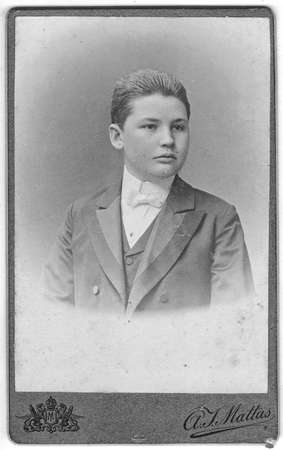 CHRUDIM, AUSTRIA - HUNGARY - CIRCA 1910: Vintage cabinet card shows portrait of the young man wearing bow tie. Photo was taken in a photo studio. Edwardian era. Photo was taken in Austro-Hungarian Empire or also Austro-Hungarian Monarchy.