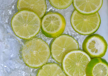 Close-up fresh slices of green limes on white background. Slices of limes in sparkling water on white background, closeup. Citrus soda Standard-Bild