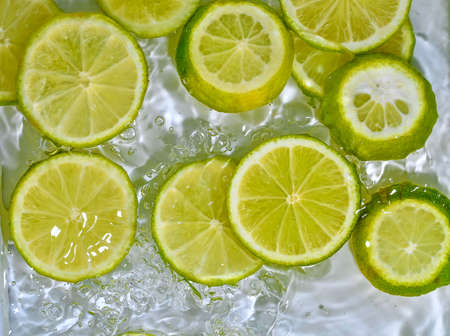 Close-up fresh slices of green limes on white background. Slices of limes in sparkling water on white background, closeup. Citrus soda. Copy space