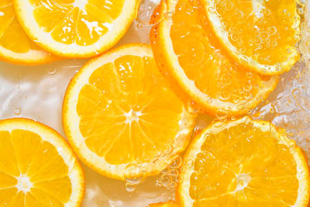 Oranges close-up in liquid with bubbles. Slices of juicy oranges in water. Close-up fresh slices of oranges on white background