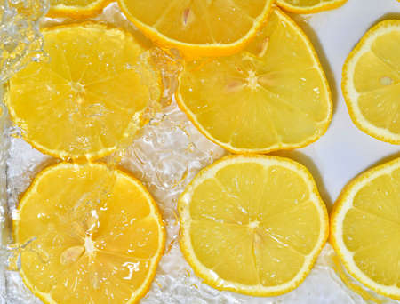 Slices of lemon in water on white background. Lemon close-up in liquid with bubbles. Slices of yellow ripe lemon in water. Macro image of fruits in water