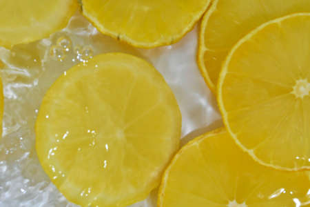 Close-up view of the yellow lemon slices in lemonade background. Texture of cooling sweet summers drink with macro bubbles on the glass wall. Flat design