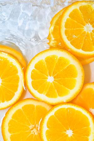 Close-up fresh slices of juicy orange on white background. Slices of orange in sparkling water on white background, closeup. Citrus soda. Copy space