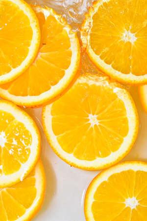 Close-up fresh slices of juicy orange on white background. Slices of orange in sparkling water on white background, closeup. Citrus soda