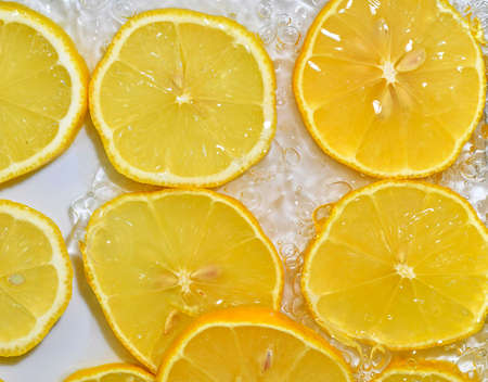 Lemon close-up in liquid with bubbles. Slices of yellow ripe lemon in water. Close-up fresh slices of lemon on white background